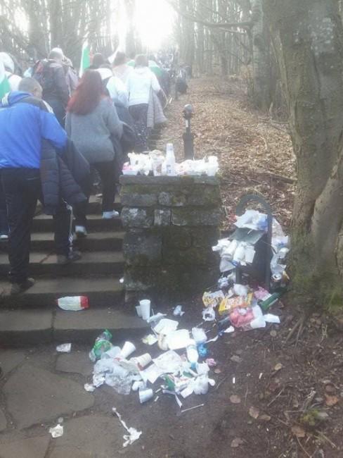 Кадър на множество хора, с патриотични знамена, заобиколени от боклуци,